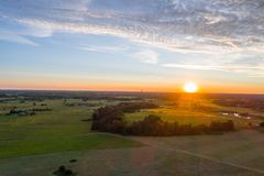 Beautiful sunset over the small town. Fields and trees around. Aerial photography. Green / yellow  summer field. Aerial photography Royalty Free Stock Image
