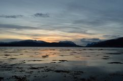 Beautiful sunset over snowy mountain range. And calm blue fjord Stock Photography