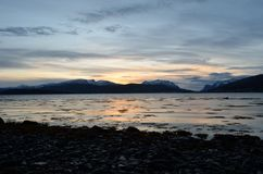 Beautiful sunset over snowy mountain range. And calm blue fjord Royalty Free Stock Image