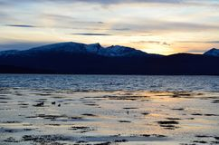 Beautiful sunset over snowy mountain range. And calm blue fjord Stock Image