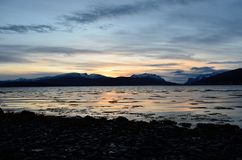 Beautiful sunset over snowy mountain range. And calm blue fjord Stock Images