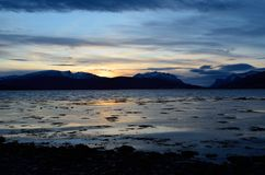 Beautiful sunset over snowy mountain range. And calm blue fjord Stock Photos