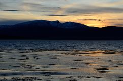 Beautiful sunset over snowy mountain range and calm blue fjord. View Royalty Free Stock Photo