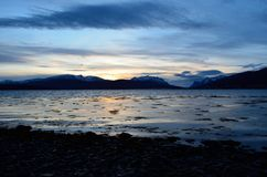 Beautiful sunset over snowy mountain range and calm blue fjord. Water Royalty Free Stock Photos