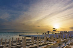 Beautiful sunset over town beach equipped with umbrellas and sunbeds. Stock Photo