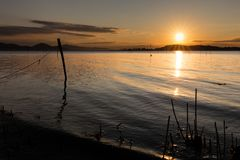 Beautiful sunset over Trasimeno lake Umbria, with sun coming down behind an island and some fishing nets in the. Beautiful sunset over Trasimeno lake Umbria with Royalty Free Stock Image