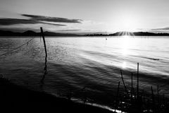 Beautiful sunset over Trasimeno lake Umbria, with sun coming down behind an island and some fishing nets in the. Beautiful sunset over Trasimeno lake Umbria with Royalty Free Stock Photo