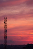Beautiful sunset over the urban landscape. Cellular tower and urban landscape on sunset sky background royalty free stock photo