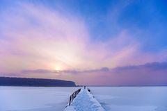 Beautiful Sunset ower Frozen River and Pier Royalty Free Stock Photography