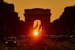 Beautiful sunset in Paris on Champs-Elysees street with Triumphal Arch. Traffic jam with lots of vehicles in Paris on Champs-Elysees street with Triumphal Arch Royalty Free Stock Images