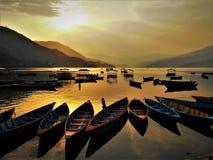 Beautiful Sunset in Phewa Lake in Nepal. Water in Phewa Lake reflect sunlight during a Beautiful Sunset in Phokara, Nepal royalty free stock image