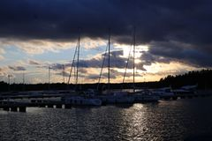 Beautiful Sunset Photographed in a Small Harbor in Finland. There is orange, yellow and blue tones in the sky. Also, the scene is gorgeously dark with amazing stock images