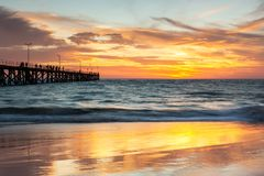 A beautiful sunset at Port Noarlunga with the jetty and sunset reflections on the sand at Port Noarlunga South Australia on 18th royalty free stock image