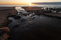 Beautiful sunset with red sand and spring water from a river exiting to the sea - Veczemju Klintis, Latvia - April 13 royalty free stock image