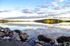 Beautiful sunset with reflection in water. Mirror summer lake. Lake Ladoga Karelia. Russia Stock Images