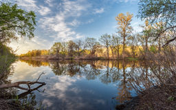 Beautiful sunset on the river in forest with sky reflection Stock Photography