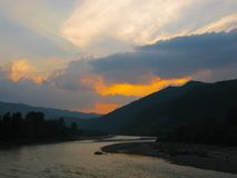 Beautiful sunset on the river with mountains stock images