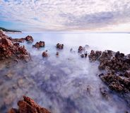 Beautiful sunset at romantic tropical beach cove with stones and water in motion Stock Image