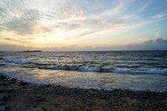 Beautiful sunset scenic wavy seaview and natural rock beach with beautiful shades of soft orange and blue sky and abstract cloud. Background, Mykonos, Greece Royalty Free Stock Photos