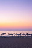 Beautiful sunset at the sea. And sunshades on the beach Stock Image