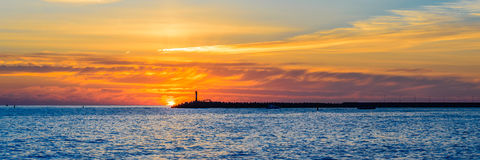 Beautiful sunset on the sea. In the background of a lonely lighthouse Stock Image