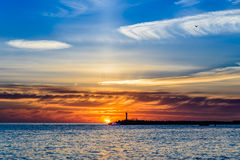 Beautiful sunset on the sea. In the background of a lonely lighthouse Royalty Free Stock Photo