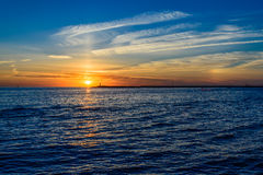 Beautiful sunset on the sea. In the background of a lonely lighthouse Royalty Free Stock Photography