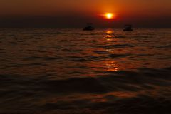 Beautiful sunset. In the distance you can see two small boats. stock photo