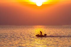 Beautiful sunset on the sea and people play water sport with lig Royalty Free Stock Photo