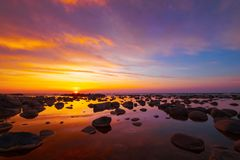 Beautiful sunset at sea side with stones stock image
