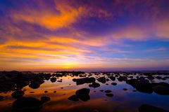 Beautiful sunset at sea side with stones royalty free stock photos
