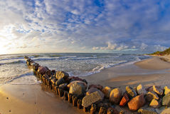 Beautiful sunset at the sea, strip of breakwaters and stones Stock Photography