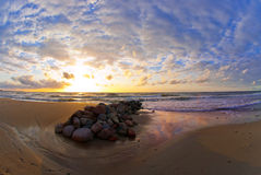 Beautiful sunset at the sea, strip of breakwaters and stones Stock Photo