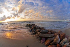 Beautiful sunset at the sea, strip of breakwaters and stones Stock Images