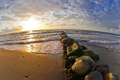 Beautiful sunset at the sea, strip of breakwaters and stones Royalty Free Stock Photos