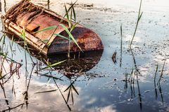 A beautiful sunset on the shore of the lake. Blurred.A strange metal rusty roller in a lake. HDR photo. stock image