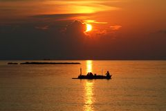 Beautiful sunset with silhouette of a small fishing boat royalty free stock photo