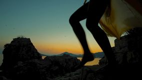 On beautiful sunset silhouette of a woman in light dress descends. stock footage
