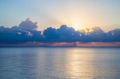 Beautiful sunset and silver path on the sea, blue clouds in the sky, background.  royalty free stock photography