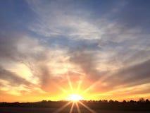 Beautiful sunset sky with the sun shining bright rays on the horizon Stock Photos