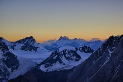 Beautiful sunset sky in the mountains view from a great altitude. Icy snowy peaks Stock Image