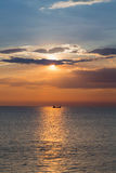Beautiful sunset sky over small fishing boat over seacoast skyline Royalty Free Stock Images
