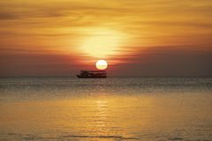 Beautiful sunset sky at sea horizontal with lonely boat floating Stock Photo