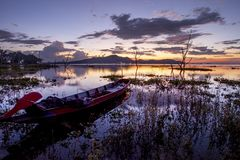 Beautiful sunset sky and wood boat floating in bangpra water res Royalty Free Stock Photography