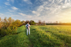 Beautiful sunset. Spring landscape with man on the field Royalty Free Stock Image