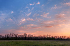 Beautiful sunset. Spring landscape with trees, blue sky and clou Stock Photos