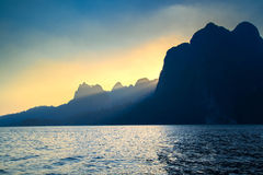 Beautiful sunset and sunbeam between mountain sunray at mountain. And sea or lake stock photo