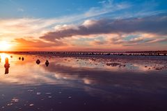 Beautiful sunset or sunrise over a salty lake, Wooden hemp in the build-up of salt after the drying of the lake stock image