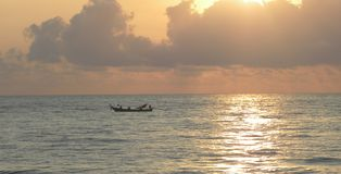 Beautiful sunset in Thailand with fishermen in the ocean. stock images