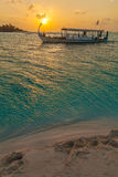 Beautiful sunset with traditional Dhoni boat, Maldives. Beautiful sunset with traditional Dhoni boat and a desert island, the Maldives Royalty Free Stock Photos